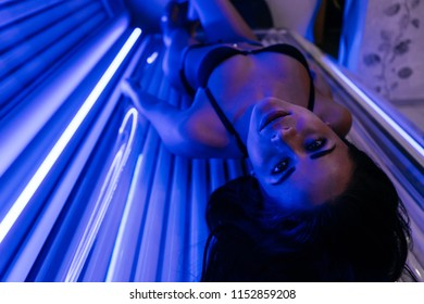 beautiful slender brunette girl in a black bathing suit lies in a sunroom, sunbathing under ultraviolet rays