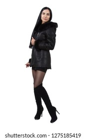beautiful slender brunette model posing in a demi-season leather jacket, short skirt and high-heeled boots. Fashion studio photo on white background. isolated.