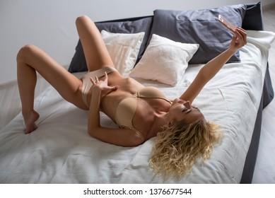 Beautiful, slender, curly blonde in light underwear, takes a selfie on the bed. Sexy girl talking on video call through the smartphone. Bedroom.
