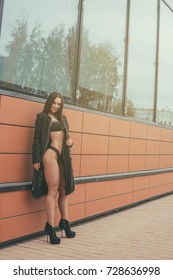 A beautiful slender dark-haired girl in a black classic coat, black underwear and high heels posing positively against the backdrop of a modern building on a warm autumn day