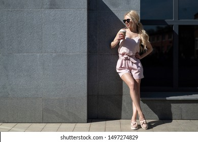 beautiful slender european girl blonde in pink tshirt and coat, sunglasses stands near gray concrete wall with glass take away coffee. copy space