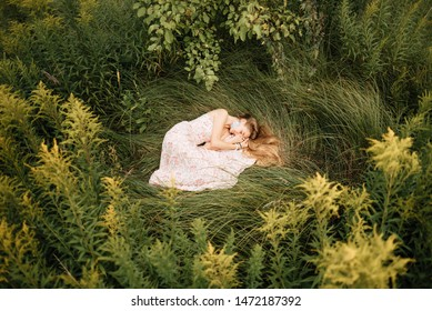 beautiful slender girl with long blonde hair in delicate dress, cute woman lies on the grass from above, fairy-tale princess in the spring garden, gentle image of the queen, fairy in love