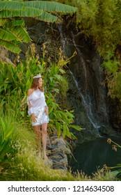 beautiful slender girl in white clothes posing near waterfalls