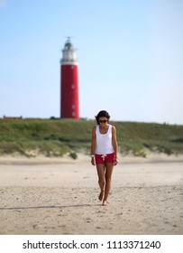 A beautiful slender model girl walks along the beach in shorts and a white T-shirt on the background of a red lighthouse. Coast of the North Sea. Netherlands.
