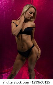 Beautiful slender tanned blonde in black lingerie on pink glitter walls