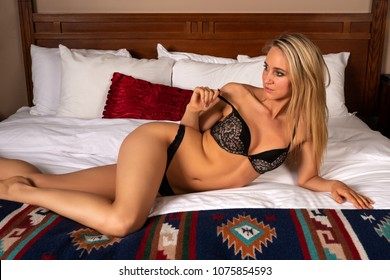 Beautiful slender tanned blonde dressed in black lingerie