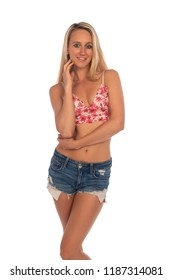 Beautiful slender tanned blonde in a flower print midriff top and denim shorts