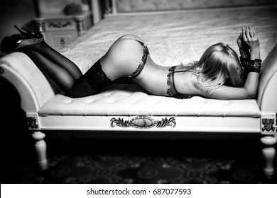 Beautiful slender woman in the bottom white lace underwear, stockings and leather handcuffs on her hands, lying bent on the sofa with her face covered with her hair, lifting her hips to the top