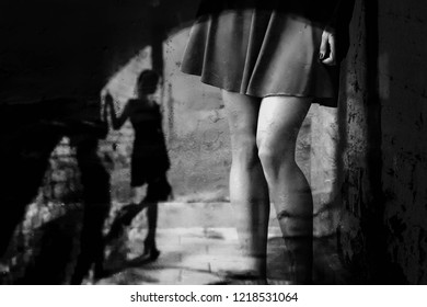 Beautiful slender women's feet in shoes and the silhouette of a girl in a dark alley (black and white photo, double exposure)