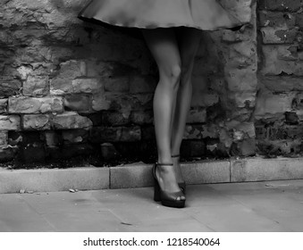 Beautiful slender women's feet in shoes in a dark alley (black and white photo)