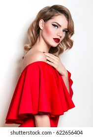 A beautiful slender young girl in a red dress and with red lips on a white background is standing. Retro hairstyle and makeup. Arrows, red lipstick. Advertising, fashion, beauty.