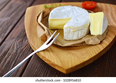 Beautiful slice of a home made cheese on a wooden plate