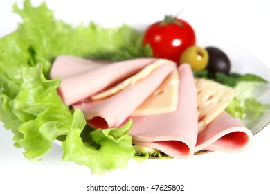 Beautiful sliced food arrangement with sausage, ripe cherry tomatoes, cheese and greenery
