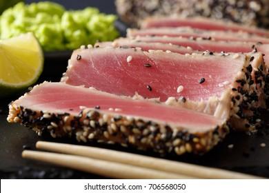 beautiful sliced tuna steak in sesame and wasabi, lime macro on the table. horizontal