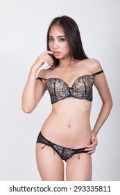 Beautiful slim body of woman in studio, white background, black long hair.