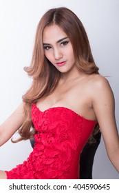 Beautiful slim body of woman in studio, white background, red dress.