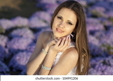 beautiful slim bride in luxury dress in park on sunset near blossom flowers in wedding day. young woman in Greek goddess style with diamond  jewelery outdoor. romantic girl with flowers