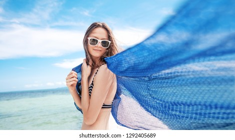 Beautiful slim brunette girl in bikini and sunglasses against the background of the blue sea, with a flying blue scarf. Leisure and travel, beauty and fashion