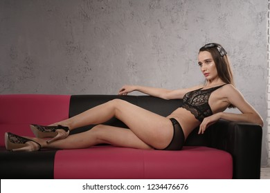 Beautiful Slim Fashion Girl Posing In the Lace Stylish Lingerie on the leather sofa alone