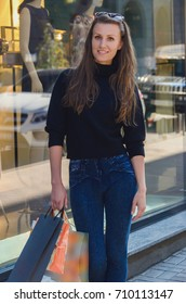 beautiful slim fashionable and stylish woman in tight jeans and a black sweater with large bags in her hands is making shopping. A woman with purchases walks by the windows of a chic store.