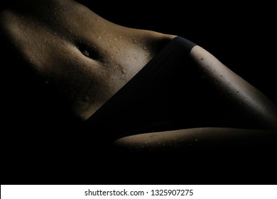 Beautiful and slim female body with drops of water and sweat on a dark background. Beautiful hips and elastic belly with a narrow waist in twilight.
