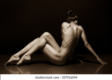 Beautiful slim female body on a dark background. Voluptuous woman's shape with clean healthy skin, muscle tonus. Spa beauty part of body. Healthy lifestyle, diet and fitness. Sepia tone.