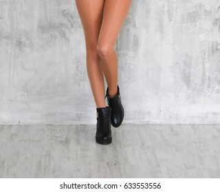 Beautiful slim female legs in light beige pantyhose and black autumn boots on grey background
