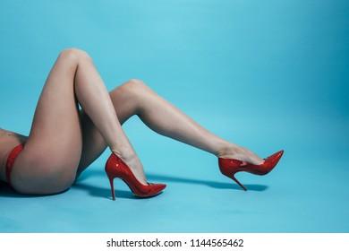 Beautiful slim female legs wearing red underwear lying on floor