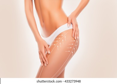 Beautiful slim fit woman touching her body with arrows isolated on beige  background