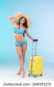 beautiful slim girl in bikini and straw hat posing with baggage and passport, isolated on blue