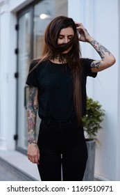 Beautiful slim girl with black lips. tattoos and piercing wearing casual  black clothes playing with hair outside. Alternative lifestyle. Portrait of tattooed young female model in black.