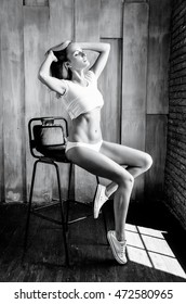 Beautiful  slim girl with blond straight hair is sitting on chair on wooden background black and white photo
