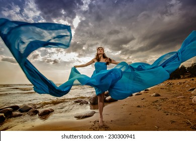 Beautiful slim girl in blue flowing dress on the sky background