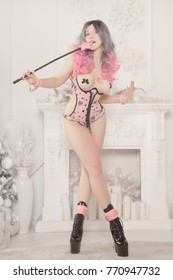 beautiful slim girl in pink lingerie standing with a bdsm riding crop with slave holders, near the christmas tree and white fireplace with new year gifts
