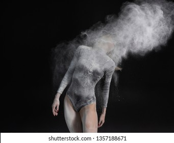 Beautiful slim girl wearing a black gymnastic bodysuit covered with white powder and dust flies from her hair on a dark. Artistic conceptual photo. Copy space