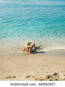 Beautiful slim senior woman tourist in bikini and hat lying on sand enjoying clear sea waters at Meditteranean resort of Turkey in Alanya, Kleopatra beach