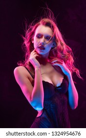 Beautiful slim sexy busty blonde girl wearing black bodysuit lit up in pink and blue light smiles and sensually touches her neck when her long hair flutters in the wind. Commercial design. Copy space