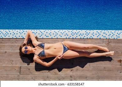 Beautiful slim sexy woman in a bikini relaxing near outdoor water pool on resort