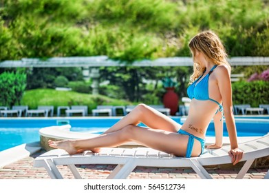 Beautiful slim sexy woman wearing blue bikini relax on beach chaise lounge near outdoor water pool. Vacation on resort