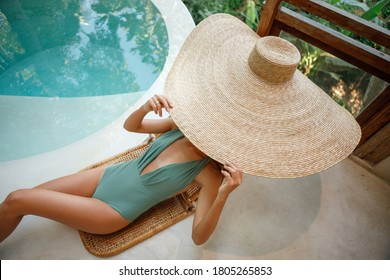 Beautiful slim tourist woman  is lying down sunbathing, covered had with huge straw hat, near round swimming pool with  clear blue water. Time to relax