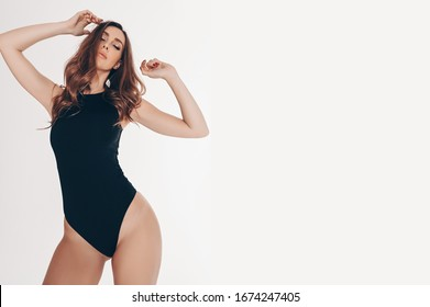Beautiful slim woman in black bodysuit  on the white background isolated. Free space for text mockup. Perfect legs with smooth soft skin. Wellness, hair removal, body care concept. Yoga & gym