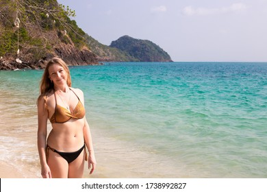 beautiful slim woman with blond long hair in a swimsuit stands on the shore of the azure sea and smiles, a paradise on the tropical coast in Asia