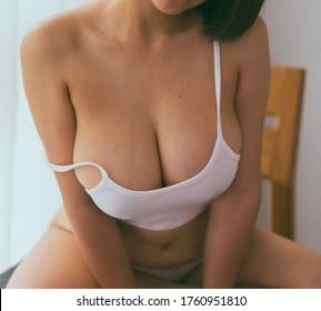 Schöne schlanke Frauenkörper im Schlafzimmer. Fügen Sie den Fotoeffekt von Vintage-Filmen hinzu.