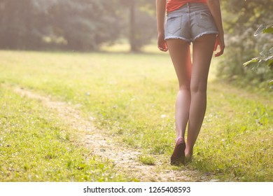 Beautiful slim woman legs in shorts in the park in summer on green grass with copy space