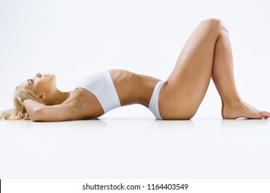 Beautiful slim woman lies in lingerie on a white background