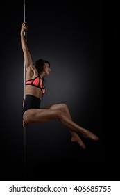 Beautiful slim woman performing pole dance on dark background