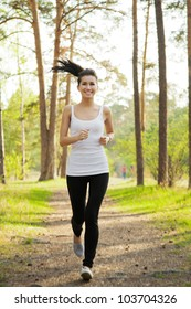 Beautiful slim woman running in the sunny park