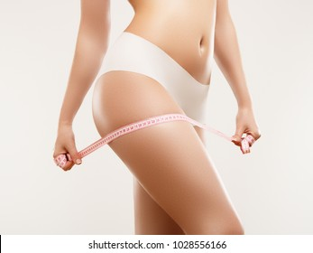 Beautiful slim woman's body. Perfect slim toned young body of the girl. Fitness or plastic surgery and aesthetic cosmetology. Firm buttocks. Beauty girl in white bikini posing on grey background