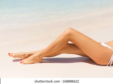 Beautiful slim woman's legs on the beach