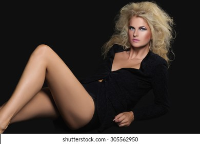 Beautiful slim young woman with bright makeup in black jacket lying on floor over black background. Studio shot.